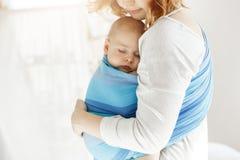 El cierre minúsculo del niño recién nacido observa y teniendo buen sueño en la protección de la sensación de la honda del bebé co fotos de archivo