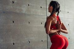 El cierre para arriba cupo a la mujer con los brazos detrás de la parte posterior que hacía estirando ejercicios fotografía de archivo libre de regalías