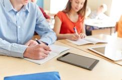 El cierre para arriba de estudiantes hace tabletas la escritura de la PC en la escuela Imágenes de archivo libres de regalías