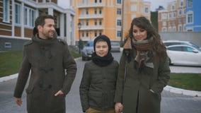 El cierre para arriba de la familia joven feliz en ropa caliente está caminando junto en la calle que ríe y que habla Padre y almacen de video