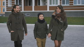 El cierre para arriba de la familia joven feliz en ropa caliente está caminando junto en la calle que ríe y que habla Padre y metrajes