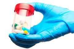 El cierre para arriba de la mano del doctor de sexo femenino en el guante quirúrgico esterilizado azul que lleva a cabo la colecc Imagen de archivo