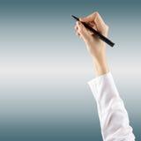 El cierre para arriba de la mano femenina está listo para dibujar con la pluma negra En azul fondo borroso Fotografía de archivo