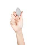 El cierre para arriba de la mano que sostiene el cosmético compone las esponjas aisladas en un fondo blanco Fotografía de archivo