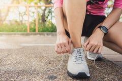 El cierre para arriba de la mujer joven ata para arriba su zapato listo al entrenamiento en el ejercicio en el parque con sol lig Fotografía de archivo libre de regalías