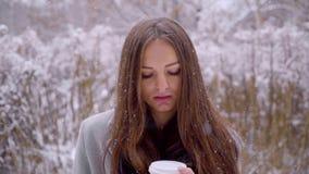 El cierre para arriba de la mujer triste hermosa joven con la taza disponible del café o de té se está sentando en un banco afuer almacen de video