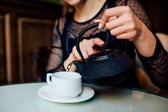 El cierre para arriba de manos de la muchacha feliz tiene taza de té verde Fotos de archivo libres de regalías