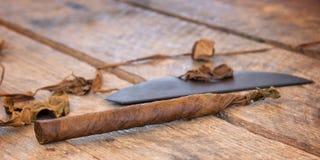 El cierre para arriba de un cigarro hecho a mano cubano con el tabaco secado se va imágenes de archivo libres de regalías