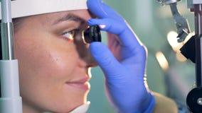El cierre para arriba de un ocular en las manos del ` s del doctor que son utilizadas para los ojos del ` s de la mujer joven con almacen de video
