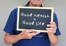 El cierre para arriba del hombre mayor que sostiene una pizarra con la buena salud de la frase iguala buena vida Imágenes de archivo libres de regalías