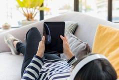 El cierre para arriba en la pantalla en blanco de la tableta con el adolescente goza Foto de archivo libre de regalías
