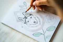 El cierre para arriba está pintando con los lápices fornido en una hoja blanca en un café en un fondo de madera blanco de la luz  imagen de archivo