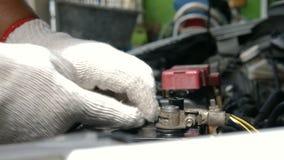 El cierre para arriba tiró al mecánico que las manos están haciendo girar el perno del zócalo de la bujía del coche almacen de metraje de vídeo