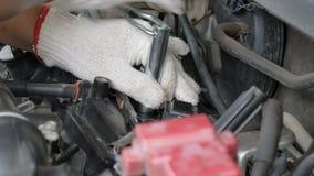 El cierre para arriba tiró al mecánico que las manos están haciendo girar el perno del zócalo de la bujía del coche almacen de video