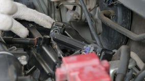 El cierre para arriba tiró al mecánico que las manos están haciendo girar el perno del zócalo de la bujía del coche metrajes