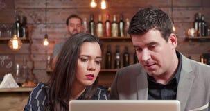 El cierre para arriba tiró de un hombre y de una mujer que miraban una pantalla y una discusión del ordenador portátil almacen de video