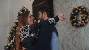 El cierre para arriba tiró de un par encantador del yound en el amor huging en el fondo del árbol de navidad almacen de video