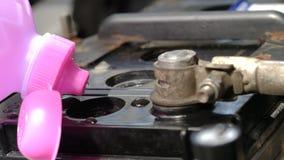 El cierre para arriba tiró las manos del repuesto de colada del agua destilada del mecánico a la fuente de batería de coche para  almacen de video