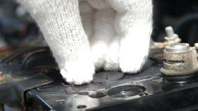 El cierre para arriba tiró las manos del repuesto de colada del agua destilada del mecánico a la fuente de batería de coche para  almacen de metraje de vídeo