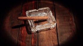 El cigarro est? mintiendo en un cenicero en una tabla de madera Iluminado por el proyector almacen de metraje de vídeo