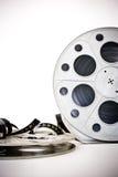el cine de la película de 35 milímetros aspa con la película desenrollada en blanco Fotos de archivo