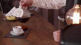 El cinemagraph fresco de a sirve la mano vierte el café de una jarra en un contador de la barra almacen de video