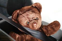 El cinturón de seguridad en la acción de la cerradura con la muñeca del oso Imagenes de archivo