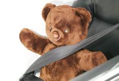 El cinturón de seguridad en la acción de la cerradura con la muñeca del oso Fotos de archivo