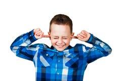 El ciose hermoso del muchacho sus oídos ignora ruido Aislado en el fondo blanco fotografía de archivo libre de regalías