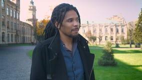 El circundar alrededor de la opinión el estudiante afroamericano con los dreadlocks que pasan a través de parque otoñal y saludo  almacen de video