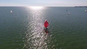 El circundar alrededor del velero con una vela roja almacen de metraje de vídeo
