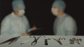 El cirujano del doctor enseña al ayudante auxiliar en el curso de cirugía, el ayudante marca y escribe a la carpeta almacen de video