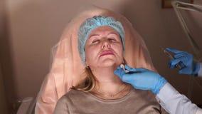 El cirujano plástico hace un tiro para una mujer adulta en el área de dobleces nasolabiales metrajes