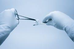 El cirujano y el ayudante cuidan las manos Fotos de archivo libres de regalías