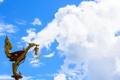 El cisne de oro esculpe la luz con el gran cielo azul Foto de archivo