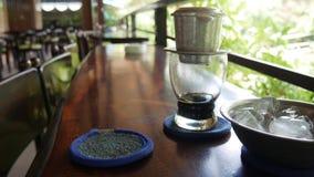El cliente bebe esperas del té helado que prepara el café sólo usando un filtro tradicional vietnamita del phin en café Goteos de almacen de video