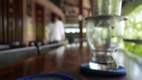 El cliente bebe esperas del té helado que prepara el café sólo usando un filtro tradicional vietnamita del phin en café Goteos de metrajes