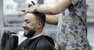 El cliente comunica con el peluquero y ríe mientras que él está cortando el pelo en barbería metrajes