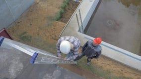 El cliente de la mujer va suavemente abajo de las escaleras que asegura un constructor del hombre en un casco almacen de video