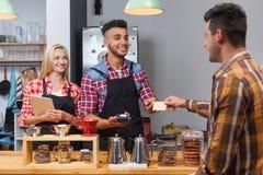 El cliente de la porción de Barista da la cuenta que paga de la tarjeta en el contador de la barra de la cafetería Imagen de archivo