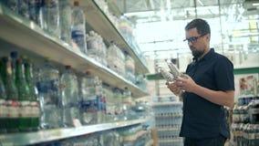 El cliente del hombre está tomando dos botellas con agua mineral del estante y de la lectura almacen de video