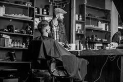 El cliente del inconformista consiguió nuevo corte de pelo Recorte acabado peluquero Peluquero con el hombre barbudo que mira el  fotografía de archivo