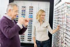 El cliente elige el vidrio del marco con ayuda del trabajador de la tienda foto de archivo libre de regalías