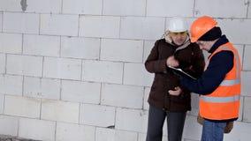 El cliente en un casco protector verifica el trabajo de constructores en el objeto bajo construcción, gente camina a través almacen de metraje de vídeo