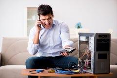 El cliente enojado que intenta reparar el ordenador con la ayuda del teléfono Fotografía de archivo