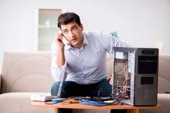 El cliente enojado que intenta reparar el ordenador con la ayuda del teléfono Imagen de archivo libre de regalías