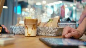 El cliente está comprando Latte para llevar del hielo y está pagando por la tarjeta de crédito en una tienda del café almacen de video