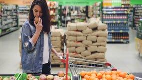 El cliente feliz de la muchacha atractiva está eligiendo la fruta en plátanos, manzanas y naranjas de compra del supermercado y l metrajes