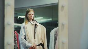 El cliente femenino atractivo está eligiendo la blusa en probador almacen de metraje de vídeo