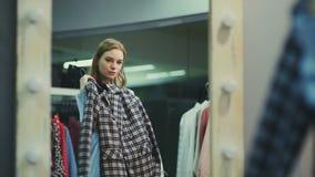 El cliente femenino atractivo está eligiendo la chaqueta en probador almacen de metraje de vídeo